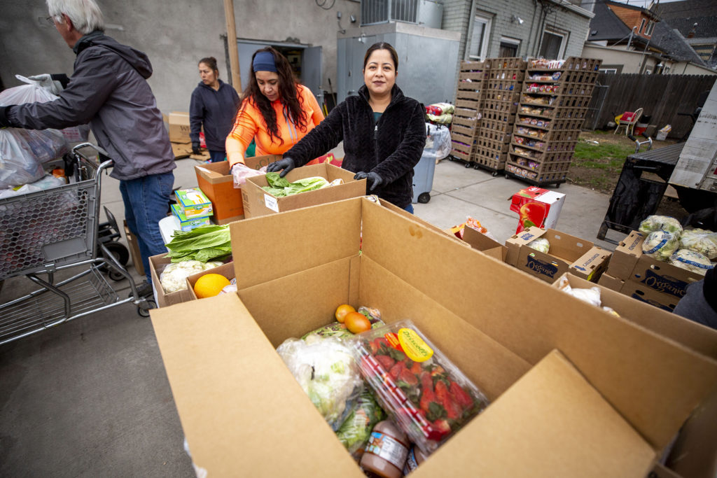 Lorena Moreno poses for a portrait as she volunteers with Twin Parishes food pantry in Cole on March 17, 2020, the first time they've had to distribute meals outside in 40 years. (Kevin J. Beaty/Denverite)