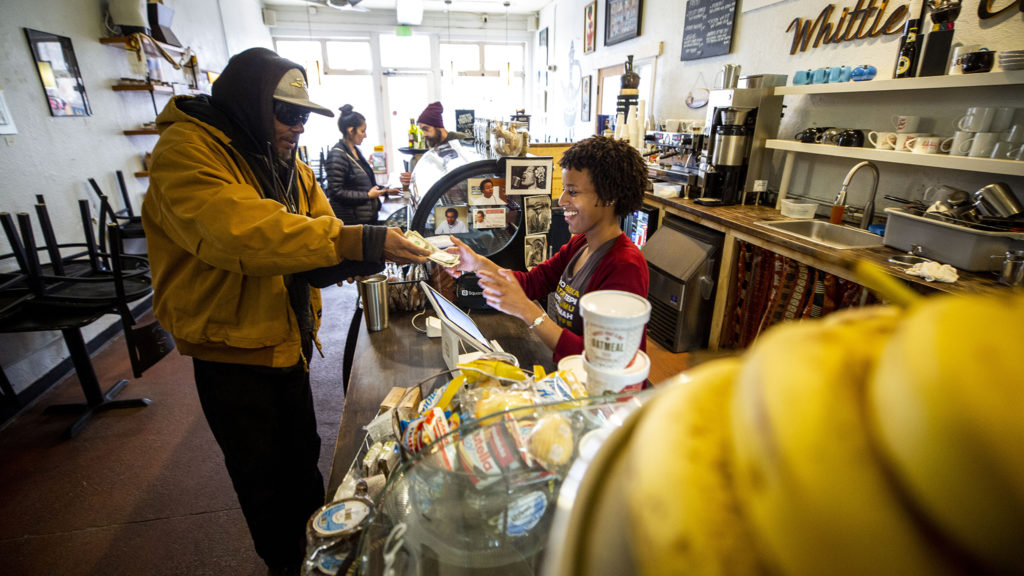 Mark Dishmon pays Sarafina Kidane for coffee at Whittier Cafe, which is closed to diners but open for to-go orders. March 17, 2020. (Kevin J. Beaty/Denverite)