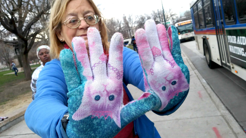 A woman named Priscilla shows off kitty gloves she said her sister gave her to wear, March 18, 2020. (Kevin J. Beaty/Denverite)