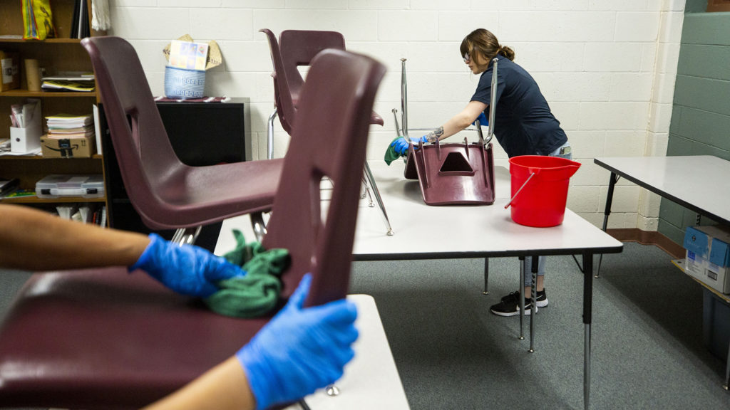 A facilities crew wipes down surfaces at Bruce Randolph School during an extended COVID-19 spring break. March 19, 2020. (Kevin J. Beaty/Denverite)
