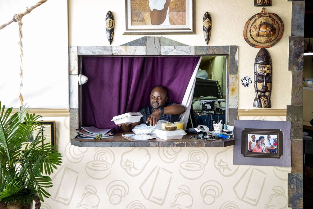 Sylvester Osei-Fordwuo, co-owner of African Grill and Bar, prepares his first pickup of the day. Green Valley Ranch, March 20, 2020. (Kevin J. Beaty/Denverite)