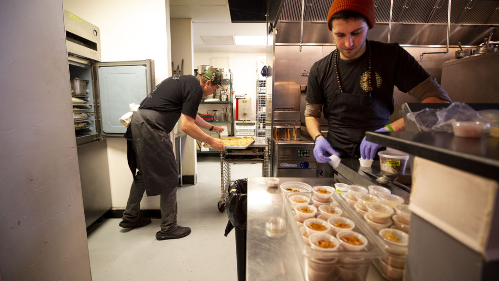 Spencer White, co-owner of Dio Mio, and James Medina prepare food for tonight's takeout orders. Five Points, March 20, 2020. (Kevin J. Beaty/Denverite)