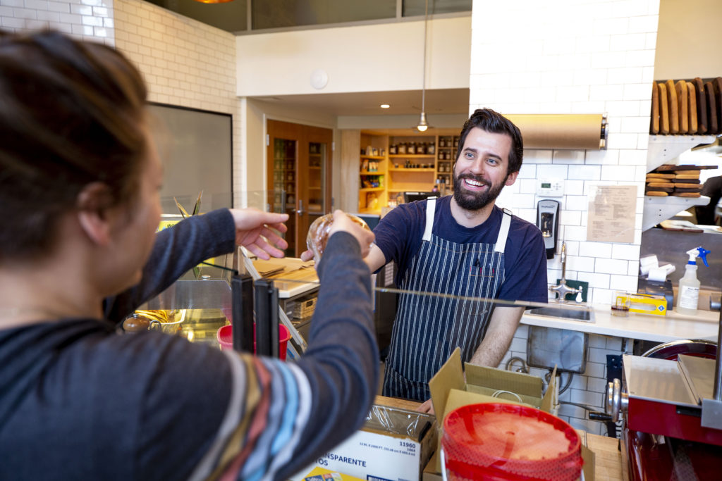 Andrew Lauer hands a sandwich to Monique Kurz inside Mercantile Dining and Provision at Union Station. March 21, 2020. (Kevin J. Beaty/Denverite)