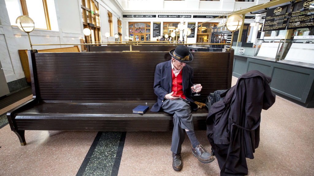 Roger Rathert brought his own glass to sip while he waits in Union Station for a train. March 21, 2020. (Kevin J. Beaty/Denverite)