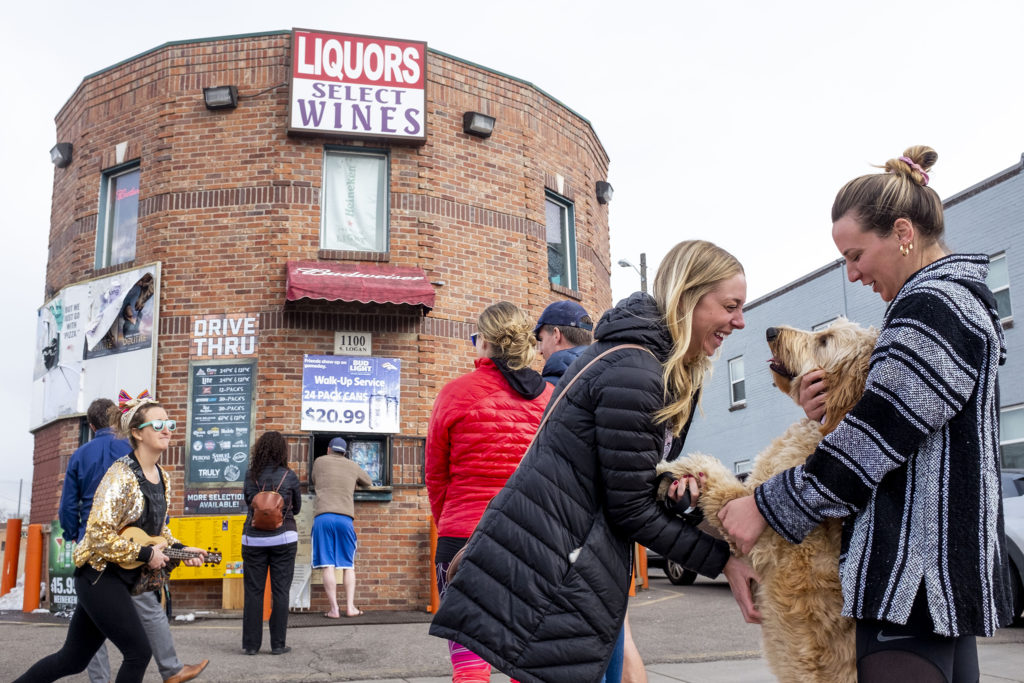Bailey Yeager and Mallory Hufford play with Rosie the dog as they wait in a long line for booze at Campus Liquor on South Logan Street, March 23, 2020. (Kevin J. Beaty/Denverite)