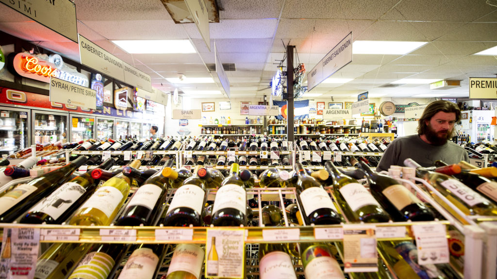 """Logan Liquors, in City Park West, can remain open as many """"nonessential"""" businesses are forced to close during the COVID-19 outbreak. March 24, 2020. (Kevin J. Beaty/Denverite)"""