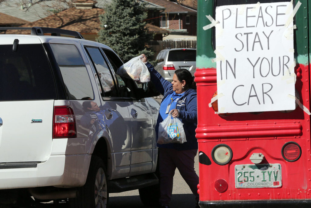 With schools closed to help stop the spread of coronavirus, Aurora Public Schools nutrition workers distribute meals to students and families from the back of a truck in the parking lot of North Middle School on Wednesday, March 25, 2020. Susana Blanco Reyes hands bags through the window of a waiting vehicle.