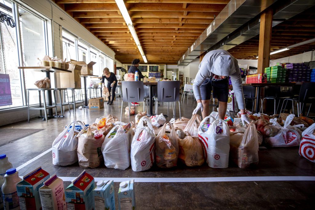 Alex Chavarria organizes groceries inside the Sun Valley Kitchen, March 25, 2020. (Kevin J. Beaty/Denverite)