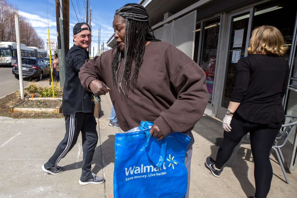 Glenn Harper bumps elbows with Stacey McCartey as she picks up groceries at Sun Valley Kitchen, March 25, 2020. (Kevin J. Beaty/Denverite)