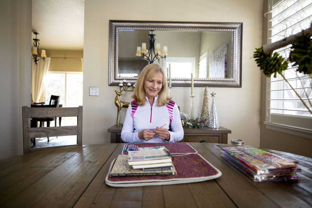 """Debbie Fox sits at the dining room table in her Arvada home where she's been making art during mandated """"social distancing."""" March 26, 2020. (Kevin J. Beaty/Denverite)"""