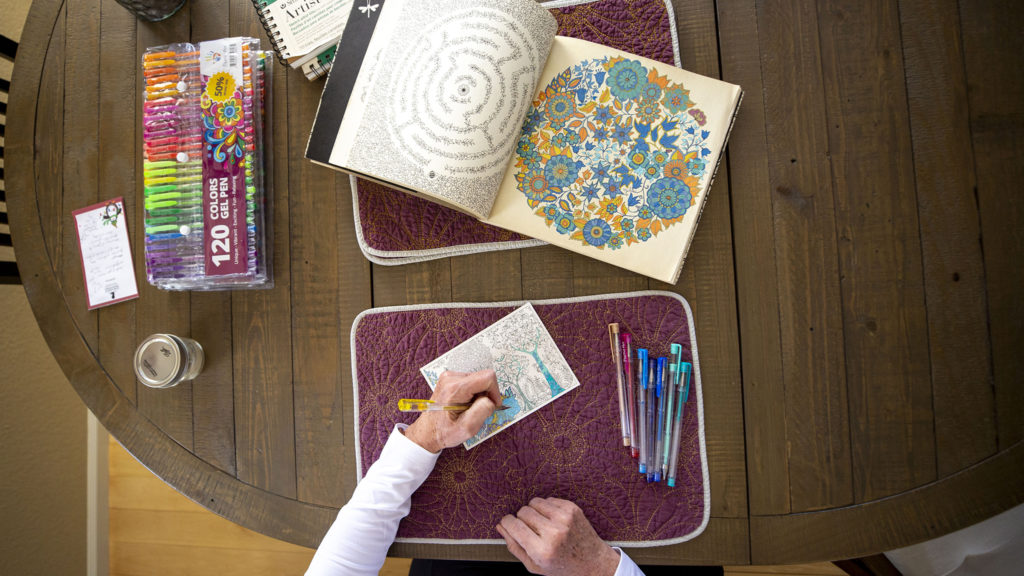Debbie Fox fills in blocks of a coloring page inside her Arvada home. March 26, 2020. (Kevin J. Beaty/Denverite)