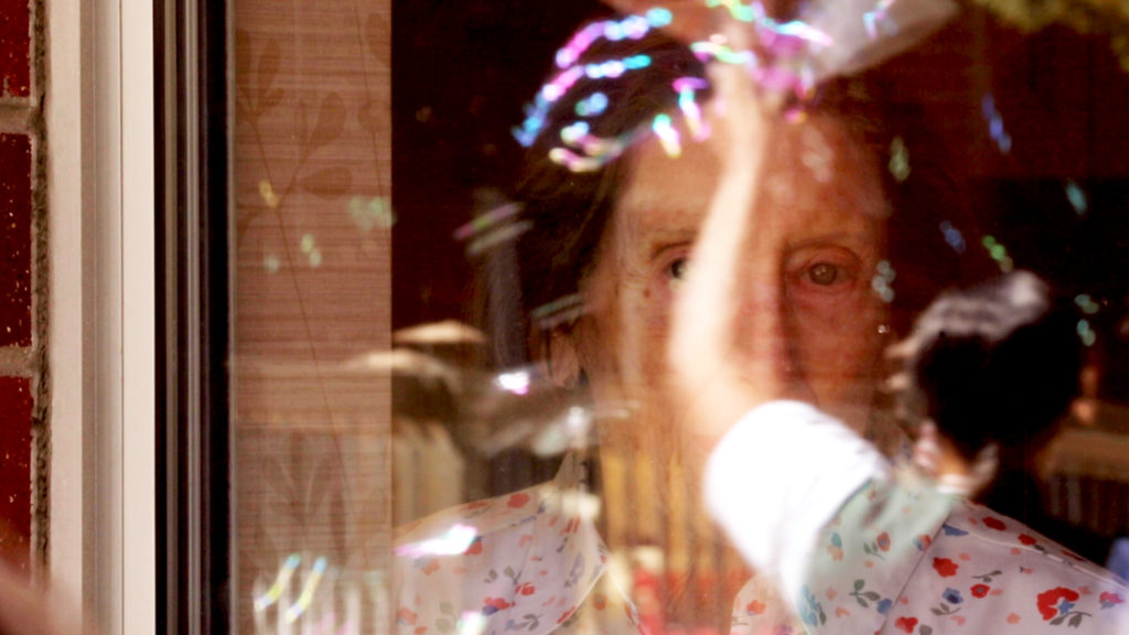 A woman watches a sing-a-long party from inside Springbrooke Senior Living center's memory care unit. Washington Virginia Vale, March 27, 2020. (Kevin J. Beaty/Denverite)