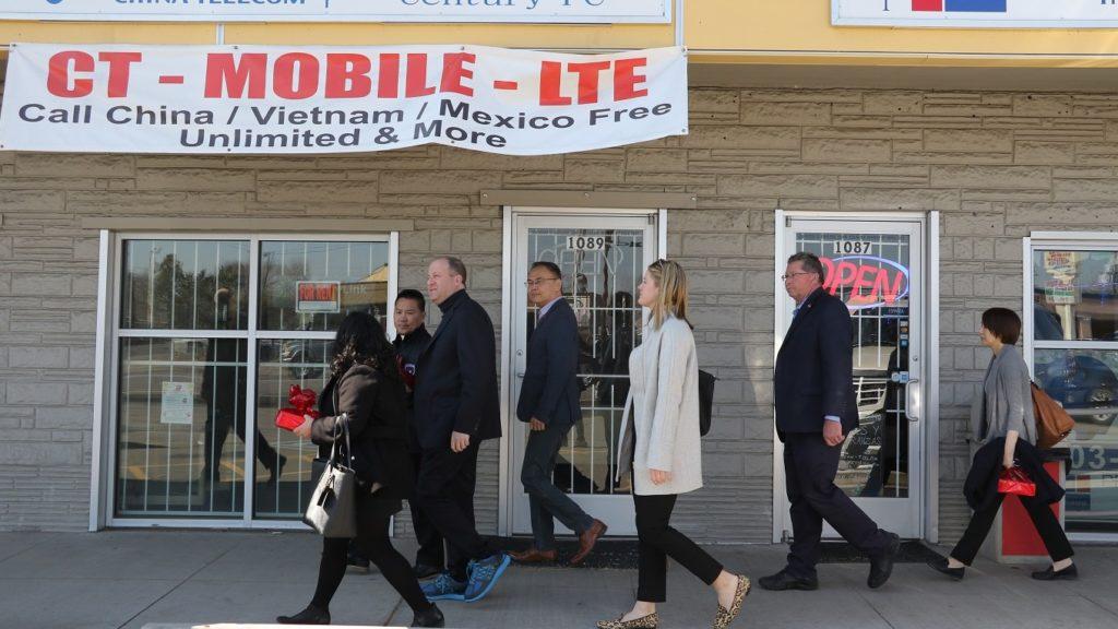 Gov. Jared Polis (center, in the blue shoes) walks down a shopping center during a tour of Asian businesses on Monday, March 2, in Denver. (Esteban L. Hernandez/Denverite)