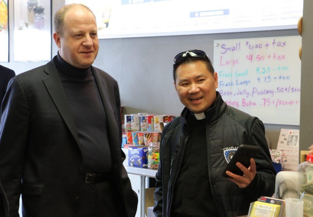 Gov. Jared Polis (left) orders boba at Lollicup with Denver police Chaplain Rev. Joseph Dang on Monday, March 3, in Denver. (Esteban L. Hernandez/Denverite)