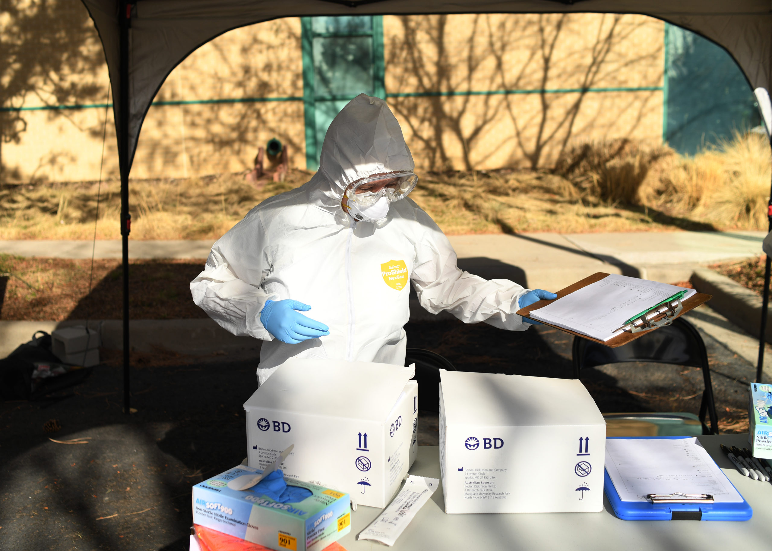 A woman sets up for the Colorado Department of Public Health and Environment first community testing center for COVID-19 at the state lab on March 11, 2020 in Denver. The drive-up testing center at 8100 E. Lowry Blvd, was open from 10 a.m. - 2 p.m for patients with doctor's order.