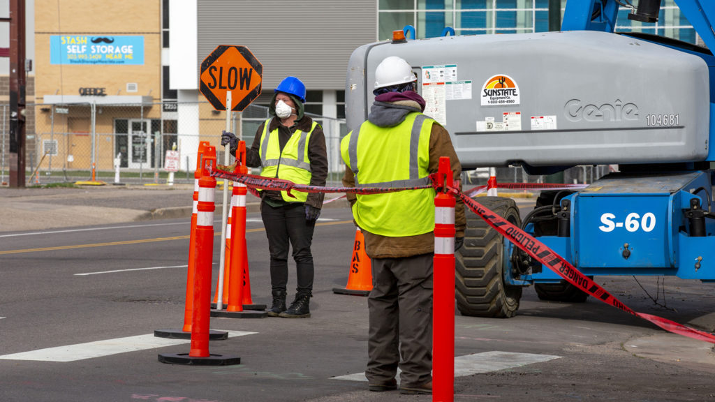 A construction flagger wears a mask at Park Avenue and Champa Street in Five Points, April 1, 2020. (Kevin J. Beaty/Denverite)