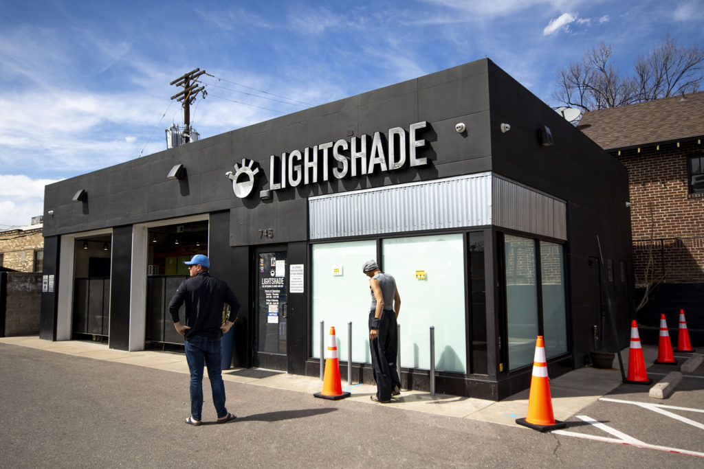 People have to wait outside to social distance before they make purchases at the Lightshade dispensary on 6th Avenue. April 1, 2020. (Kevin J. Beaty/Denverite)