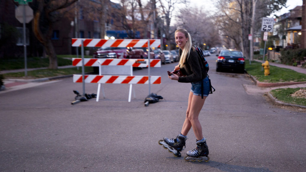 A woman named Kate rollerblades with a ukulele in the Cheesman Park neighborhood. April 7, 2020. (Kevin J. Beaty/Denverite)