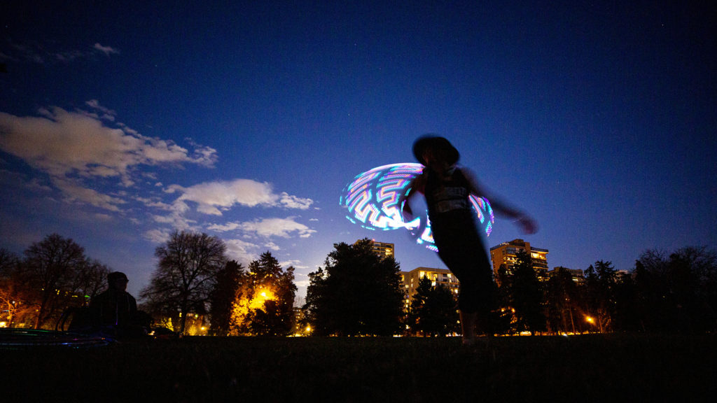 Heather Farley whips a hula hoop around her body in Cheesman Park. April 7, 2020. (Kevin J. Beaty/Denverite)