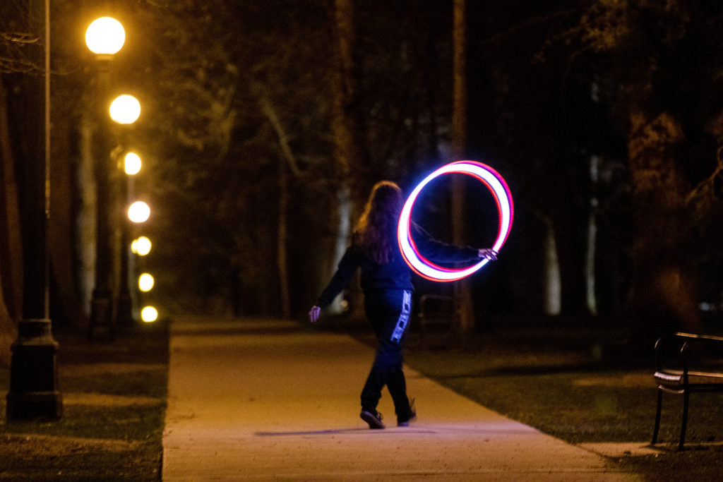 A woman walks through Cheesman Park with a glowing hula hoop. April 7, 2020. (Kevin J. Beaty/Denverite)