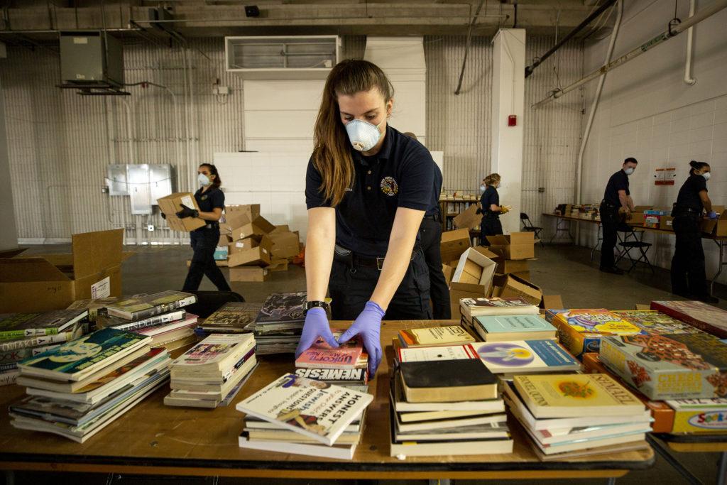 Vasi Reiva, a Denver Division of Public Safety cadet, helps set up a library inside the makeshift shelter for unhoused men at the National Western Center. April 8, 2020. (Kevin J. Beaty/Denverite)