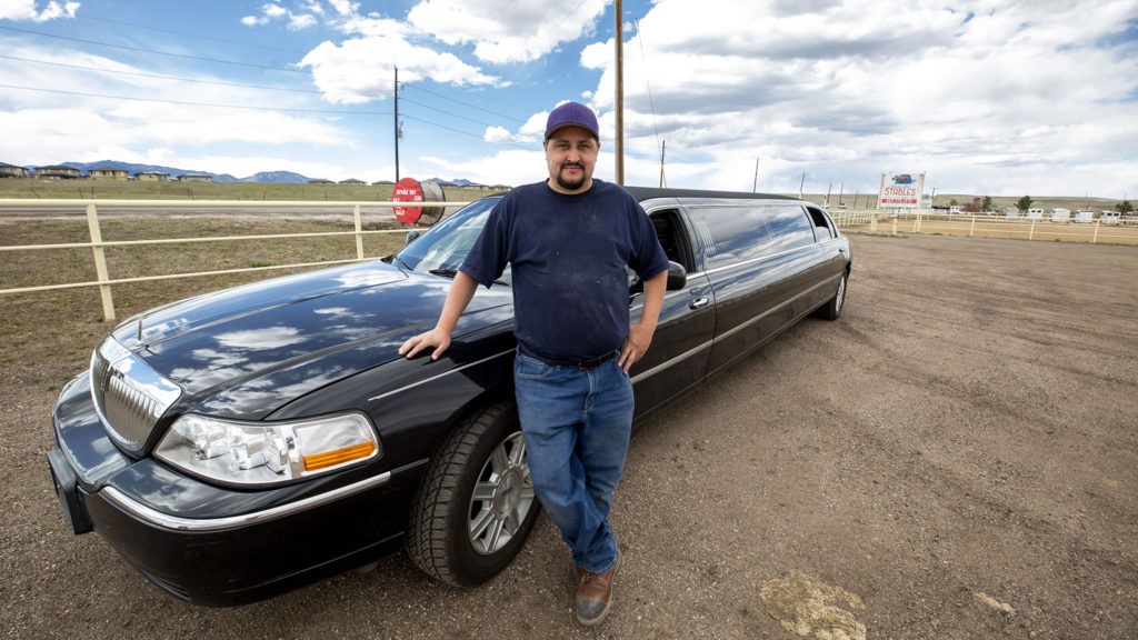 David Lawrence stands with one of his limousines at an Arvada stable. April 10, 2020. (Kevin J. Beaty/Denverite)