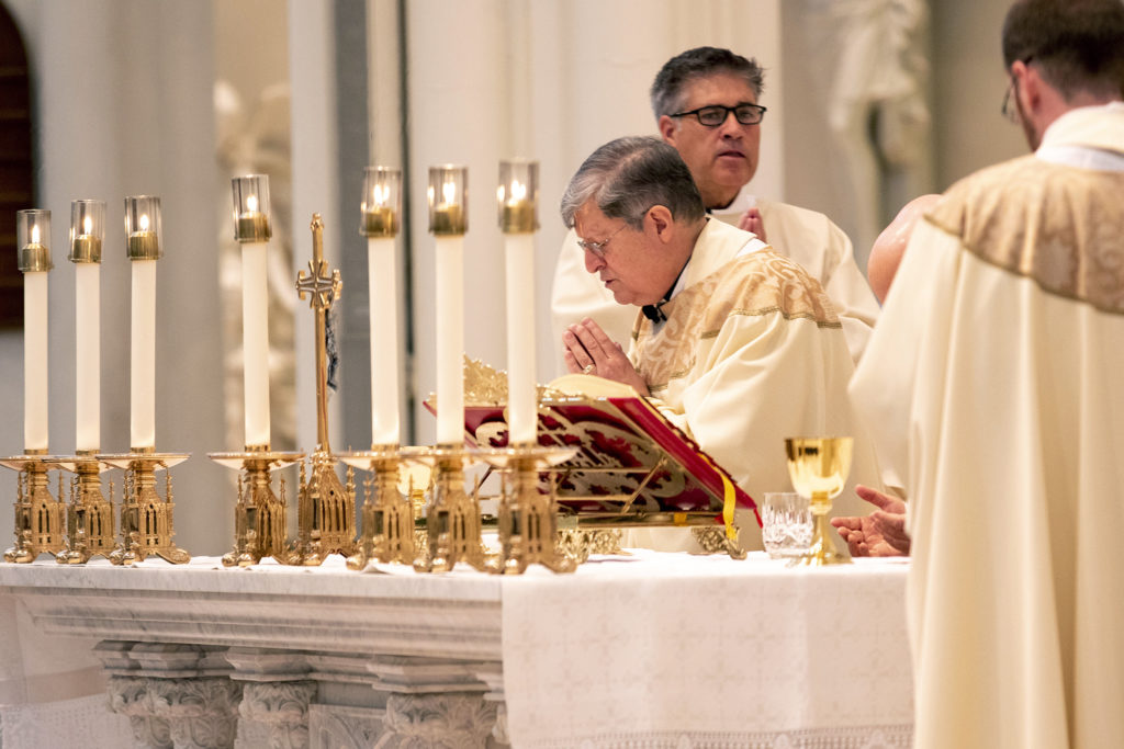 Father Ron Cattany prays during Easter mass at the Cathedral Basilica of the Immaculate Conception. April 12, 2020. (Kevin J. Beaty/Denverite)