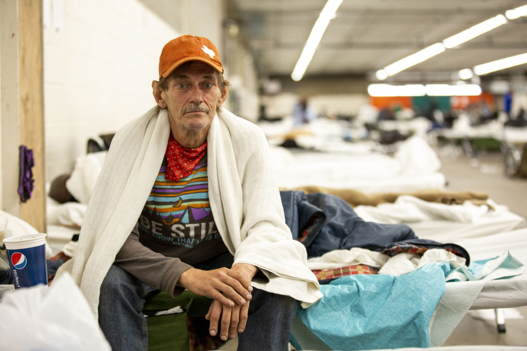 """Dennis Buckler sits on his bed inside the National Western Center's makeshift sheter for the unhoused on April 15, 2020. He said he ended up in Denver when he was bumped from a connecting flight to Kansas City. This shelter, he said, is being run """"really good."""" (Kevin J. Beaty/Denverite)"""