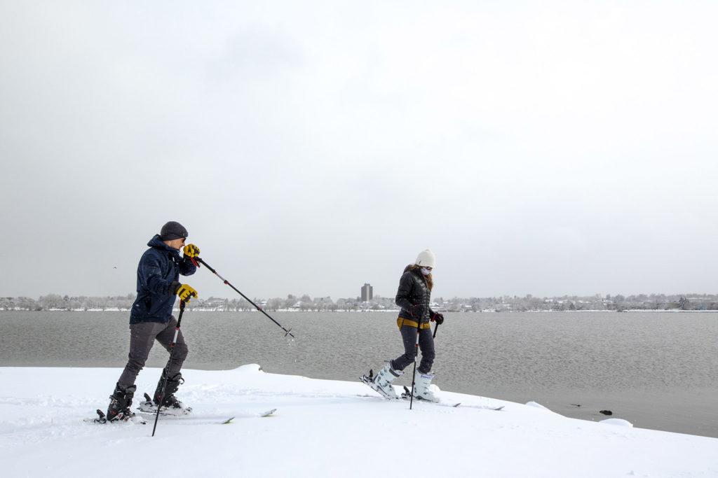 M. Hecker and Meaghan Elek ski around Sloan's Lake on a cold, foggy evening. April 16, 2020. (Kevin J. Beaty/Denverite)