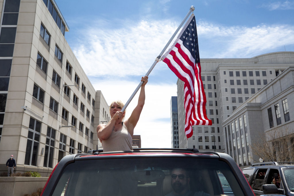 Rhonda Bovadilla holds an American flag in a truck bed as protesters demand the end to Colorado's stay-at-home order at the state Capitol building. April 19, 2020. (Kevin J. Beaty/Denverite)