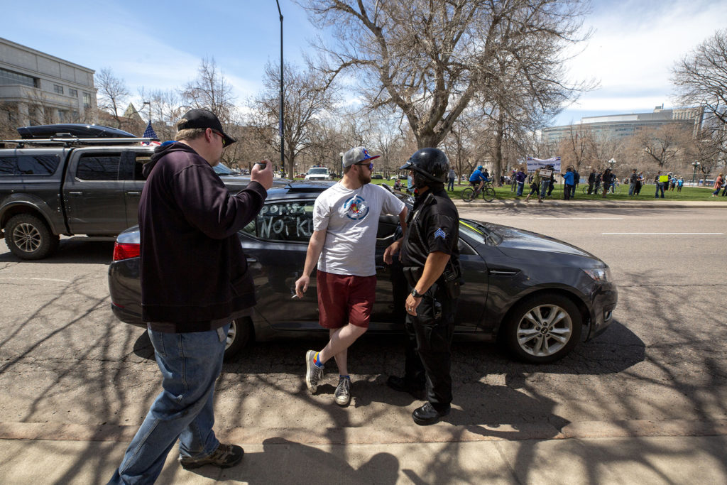 A Denver Police officer tells Frank Gallagher to move his car as protesters drive around at the state Capitol building, demanding an end to Colorado's stay-at-home order. April 19, 2020. (Kevin J. Beaty/Denverite)