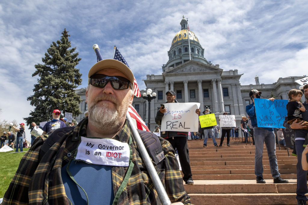 """A man who declined to be named wears a mask that reads """"My governor is an idiot"""" at a protest demanding the end to Colorado's stay-at-home order. April 19, 2020. (Kevin J. Beaty/Denverite)"""