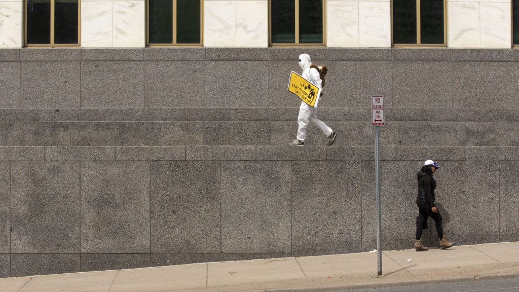 A man in a hazmat suit carrys a sign while, at the state Capitol across the street, protesters demand the end to Colorado's stay-at-home order. April 19, 2020. (Kevin J. Beaty/Denverite)