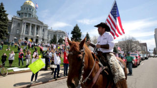 Couy Griffin rides a horse up Lincoln Street as protesters demand the end to Colorado's stay-at-home order at the state Capitol building. April 19, 2020. (Kevin J. Beaty/Denverite)