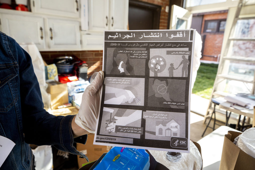 Michelle Lasnier, owner of Ruby's Pantry, holds up a COVID-19 info sheet that's been translated into Arabic. April 21, 2020. (Kevin J. Beaty/Denverite)