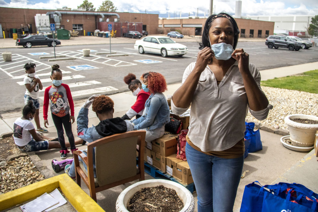 LaKeisha Hodge, with the Struggle of Love Foundation, stands near the food pantry operation she's helping to run in Montbello. April 24, 2020. (Kevin J. Beaty/Denverite)