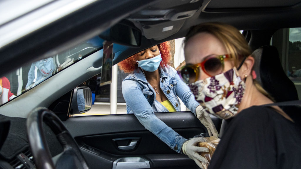 Daijahrry Ward drops a loaf of bread into Emily Cooley's car at the Struggle of Love Foundation's Montbello food pantry. April 24, 2020. (Kevin J. Beaty/Denverite)
