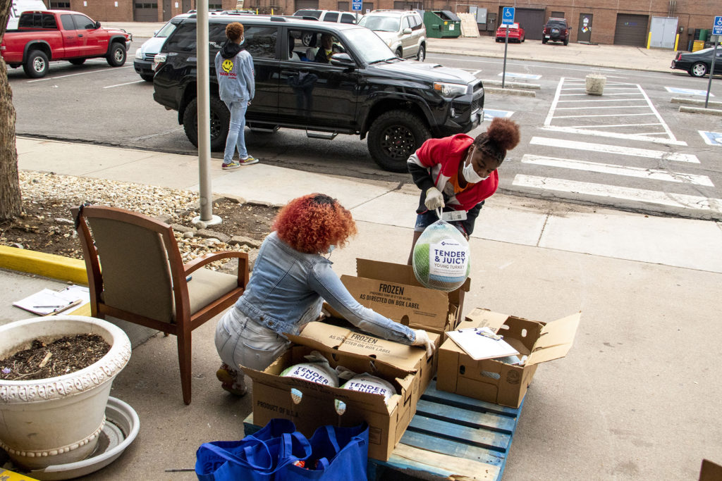 Anthoney Neal (left to right), Daijahrry Ward and Janiyah Webster help distribute grocery bags at the Struggle of Love Foundation's Montbello food pantry. April 24, 2020. (Kevin J. Beaty/Denverite)