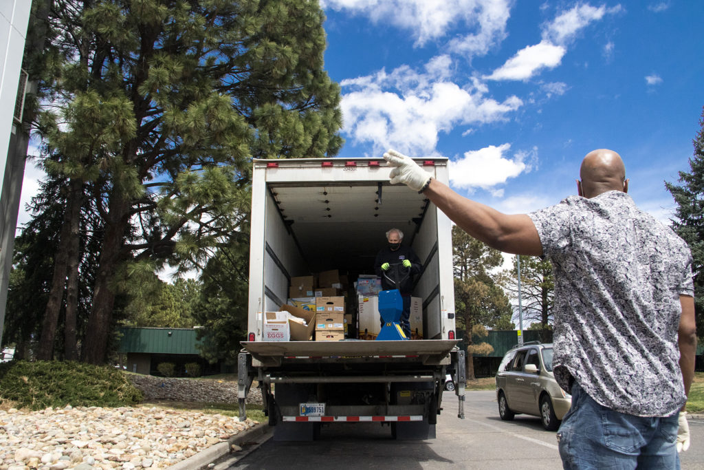 Theo Wilson directs traffic at the Struggle of Love Foundation's Montbello food pantry. April 24, 2020. (Kevin J. Beaty/Denverite)
