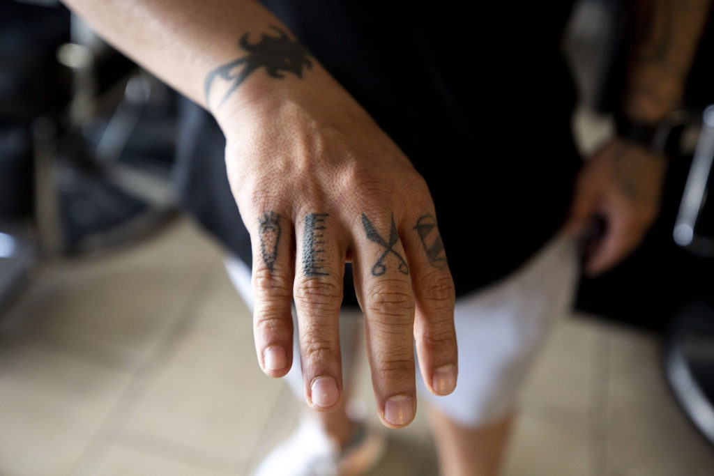 Francisco Martinez, owner of Cisco's Barbershop, shows off his thematic tattoos. April 25, 2020. (Kevin J. Beaty/Denverite)