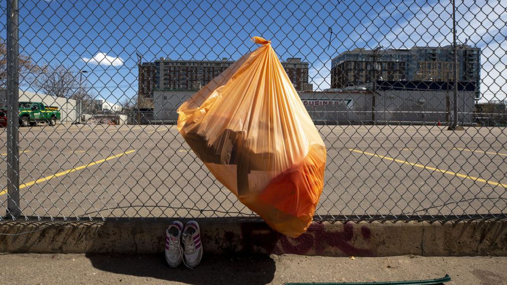 A trash bag and a pair of shoes near encampments along Stout Street. April 28, 2020. (Kevin J. Beaty/Denverite)