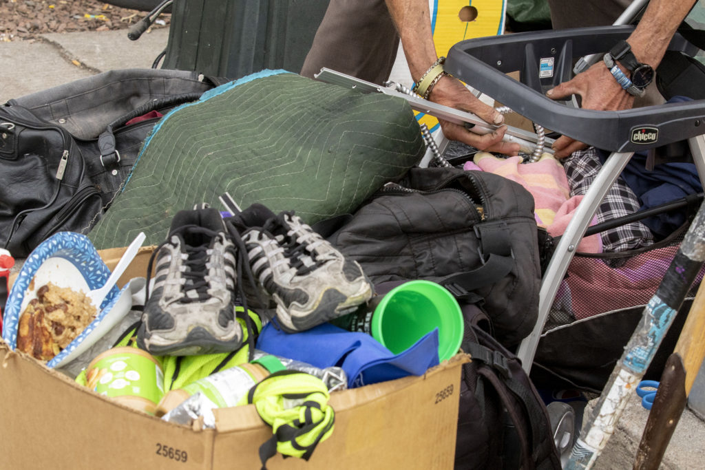 Robert Quillen packs up his stuff during a multi-agency cleanup of homeless encampments near the intersection of 22nd and Champa Streets in Five Points. April 30, 2020. (Kevin J. Beaty/Denverite)