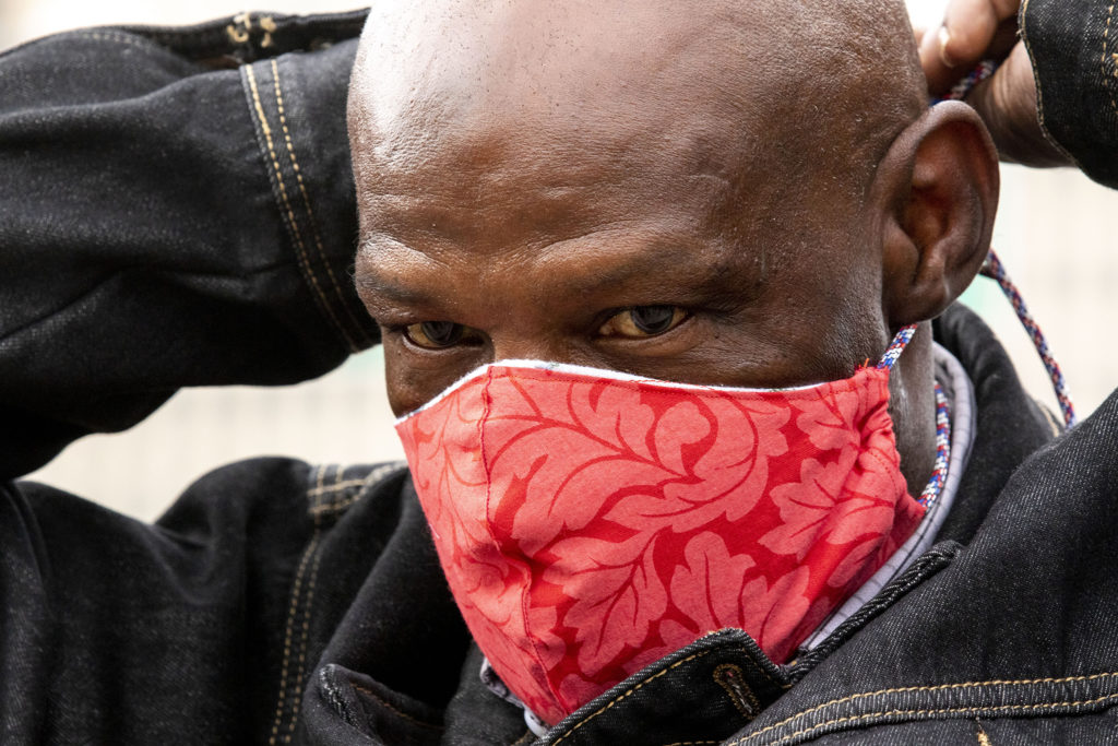 Homeless-rights activist Jerry Burton ties a mask over his face during a multi-agency cleanup of homeless encampments near the intersection of 22nd and Champa Streets in Five Points. April 30, 2020. (Kevin J. Beaty/Denverite)