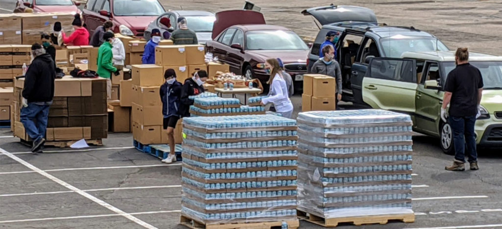 A Food Bank of the Rockies senior box and family food distribution takes place in the parking lot of a school, Academy 360 in Montbello, on April18, 2020. The school's lot allowed more space than the food bank's own warehouse nearby for a drive-through distribution, a model that reduces the person-to-person contact that can spread the coronavirus. (Donna Bryson/Denverite)