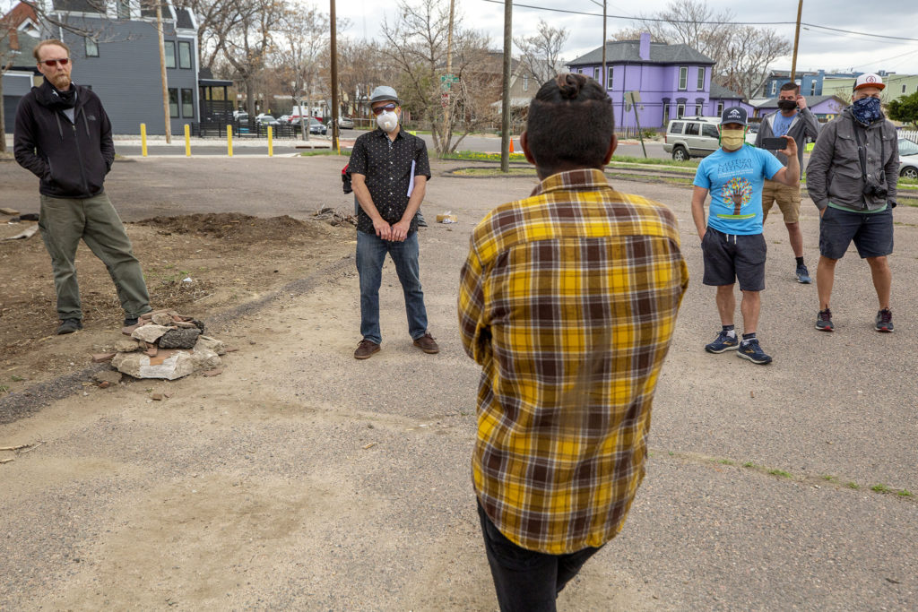 Reggie Bradford speaks to Matthew Kinner (left to right), Jeff Baker, John Hayden and his husband, Keith, and Bradley Joseph in the vacant lot at 33rd and Curtis Streets. May 2, 2020. (Kevin J. Beaty/Denverite)