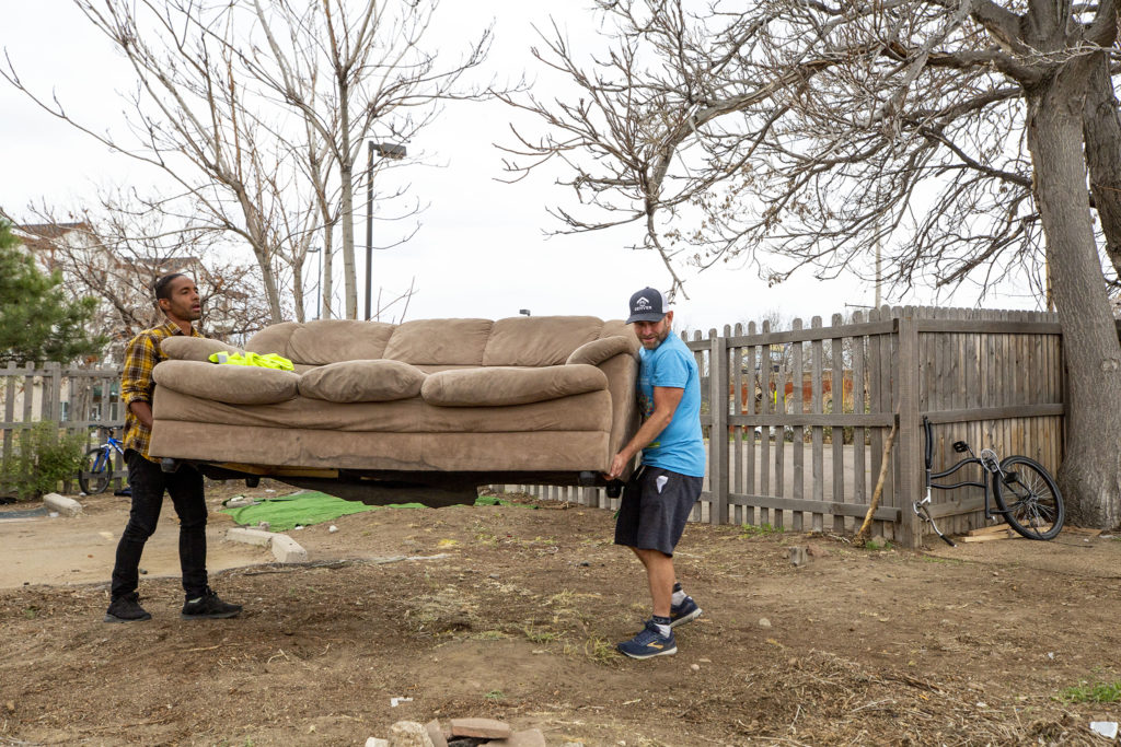 John Hayden and Reggie Bradford carry a couch to the edge of the vacant lot at 33rd and Curtis Streets in Five Points. May 2, 2020. (Kevin J. Beaty/Denverite)