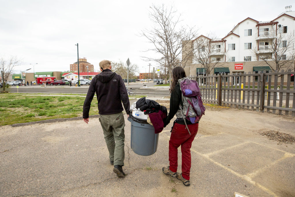 Matthew Kinner and Terese Howard carry trash out of Kinner's lot at 33rd and Curtis Streets in Five Points. May 2, 2020. (Kevin J. Beaty/Denverite)
