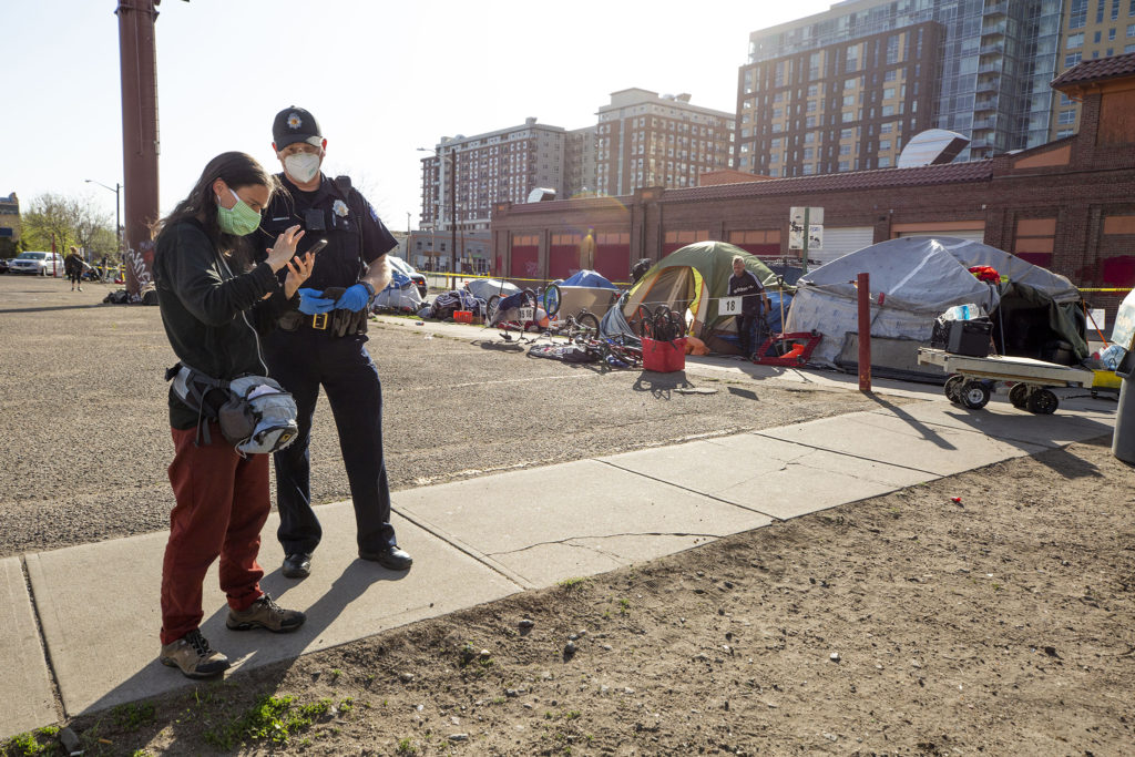 Terese Howard, with Denver Homeless Out Loud, speaks to Denver Police Sgt. Brian Conover as his officers instruct people living on the street in Five Points to pack up and move for sidewalk cleaning. May 7, 2020. (Kevin J. Beaty/Denverite)