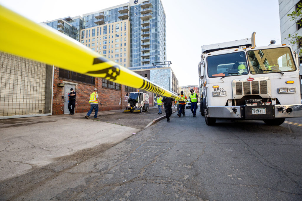 Crews clean the sidewalk along 21st Street in Five Points. May 7, 2020. (Kevin J. Beaty/Denverite)