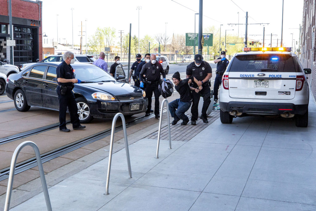 A man is arrested after he allegedly hit a police car with a baseball bat during a sweep of Denver's unhoused in Five Points. May 7, 2020. (Kevin J. Beaty/Denverite)